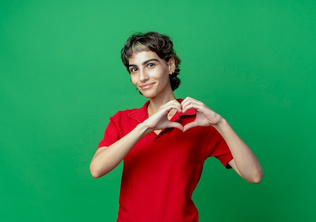 Zadowolona młoda dziewczyna kaukaski z fryzurą pixie robi znak serca na białym tle na zielonym tle z miejsca na kopię
