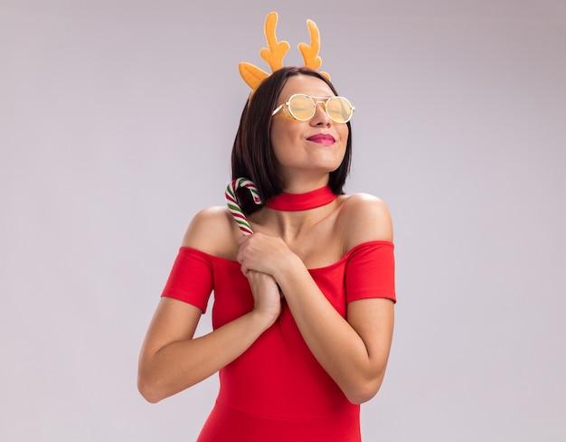 Zadowolona młoda dziewczyna nosi opaskę z poroża renifera i okulary, trzymając boże narodzenie boże narodzenie trzciny cukrowej z zamkniętymi oczami na białym tle z miejsca kopiowania