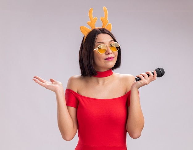 Zadowolona młoda dziewczyna nosi opaskę z poroża renifera i okulary, trzymając mikrofon, patrząc na kamery pokazując pustą rękę na białym tle