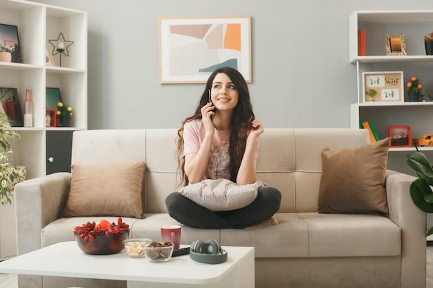 Zadowolona młoda dziewczyna rozmawia przez telefon, siedząc na kanapie za stolikiem kawowym w salonie