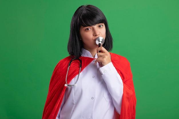 Zadowolona młoda dziewczyna superbohatera w stetoskopie z medycznym szlafrokiem i płaszczem całuje stetoskop na białym tle na zielonej ścianie