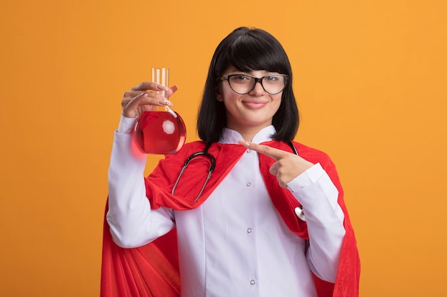 Zadowolona młoda dziewczyna superbohatera w stetoskopie z szatą medyczną i płaszczem w okularach trzymająca i wskazująca na szklaną butelkę chemiczną wypełnioną czerwonym płynem