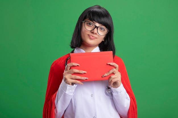 Zadowolona młoda dziewczyna superbohatera w stetoskopie z szlafrokiem i płaszczem w okularach, trzymając książkę na białym tle na zielonej ścianie
