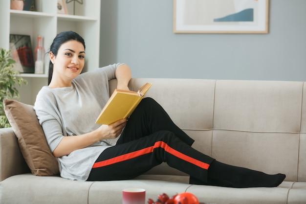 Zadowolona młoda dziewczyna trzyma książkę leżącą na kanapie za stolikiem kawowym w salonie