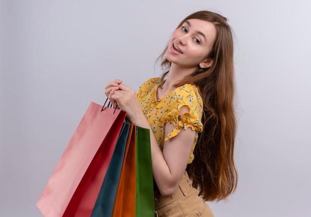 Zadowolona młoda dziewczyna trzyma papierowe torby stojąc w widoku profilu