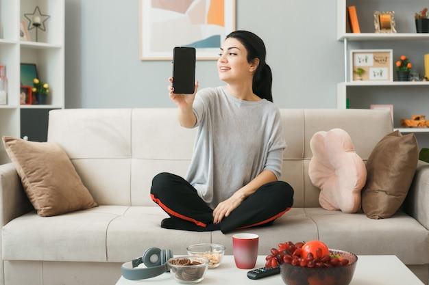 Zadowolona młoda dziewczyna trzyma telefon, siedząc na kanapie za stolikiem kawowym w salonie