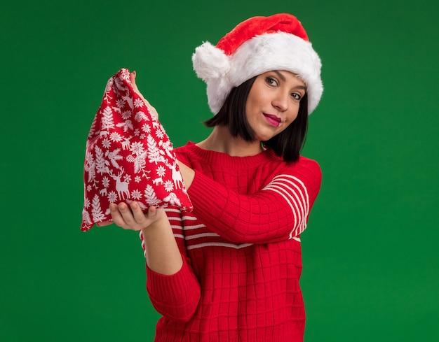 Zadowolona młoda dziewczyna ubrana w santa hat wyciągający worek prezentów bożonarodzeniowych na białym tle na zielonej ścianie