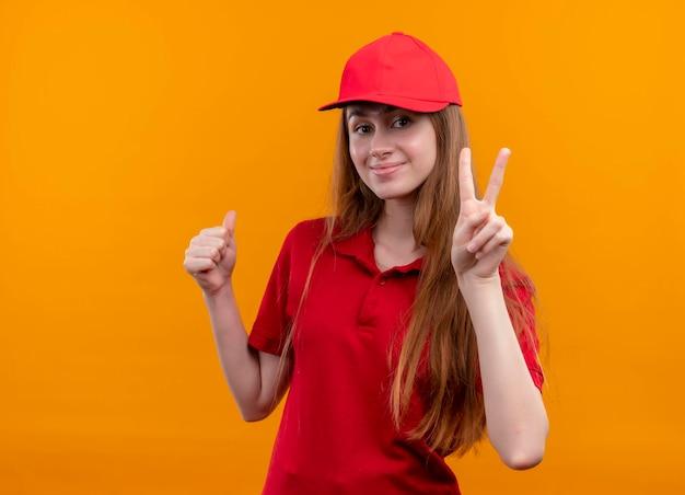Zadowolona młoda dziewczyna w czerwonym mundurze robi znak pokoju i pokazuje kciuk w górę na odizolowanej pomarańczowej przestrzeni z miejscem na kopię