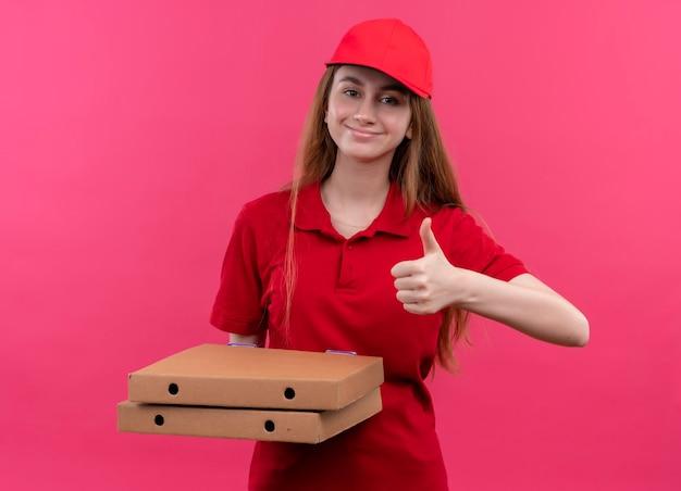 Zadowolona młoda dziewczyna w czerwonym mundurze trzyma paczki i pokazuje kciuk w górę na odizolowanej różowej przestrzeni