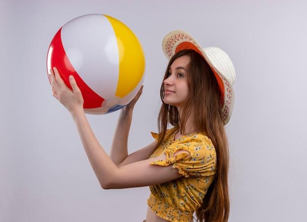 Zadowolona młoda dziewczyna w kapeluszu podnosząca piłkę plażową stojącą w widoku profilu na odosobnionej białej przestrzeni