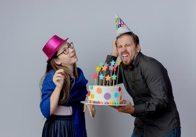Zadowolona młoda dziewczyna w okularach w różowym kapeluszu trzyma gwizdek patrząc w górę i zirytowany przystojny mężczyzna w czapce urodzinowej trzyma tort i kładzie rękę na głowie na białej ścianie