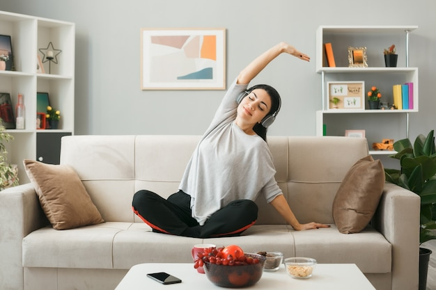 Zadowolona młoda dziewczyna w słuchawkach robi jogę, siedząc na kanapie za stolikiem kawowym w salonie