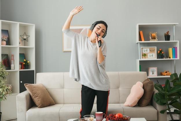 Zadowolona młoda dziewczyna z rozłożonymi dłońmi w słuchawkach trzymająca pilota od telewizora śpiewa stojąca za stolikiem kawowym w salonie