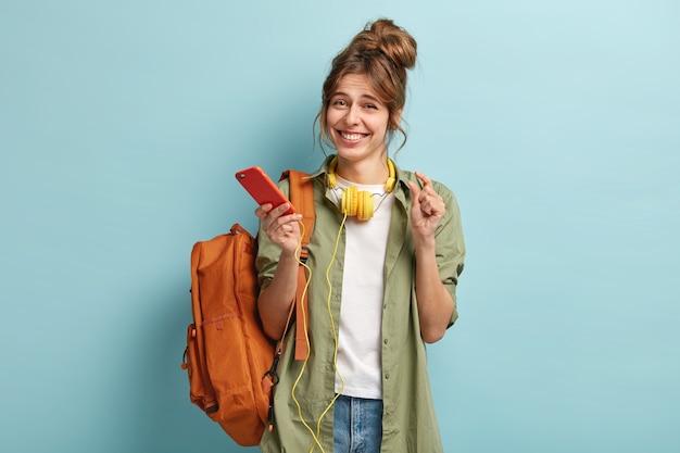 Zadowolona młoda europejka pokazuje coś ręką, lubi wolny czas i surfuje po internecie przez telefon komórkowy