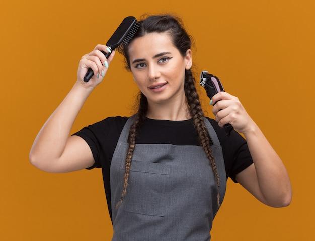 Zadowolona młoda fryzjerka w mundurze trzymająca maszynki do strzyżenia włosów i czesząca włosy odizolowane na pomarańczowej ścianie