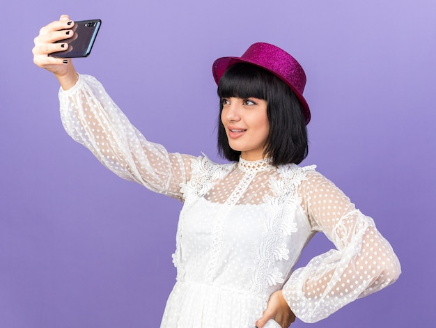 Zadowolona młoda imprezowa kobieta w imprezowym kapeluszu stojąca w widoku profilu, trzymająca rękę w talii, biorąca selfie izolowane na fioletowej ścianie
