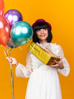 Zadowolona młoda imprezowa kobieta w imprezowym kapeluszu, trzymająca balony i pakiet prezentów, patrząc w górę odizolowana na pomarańczowej ścianie