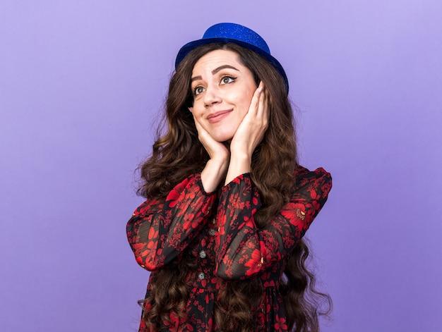Zadowolona młoda imprezowa kobieta w imprezowym kapeluszu trzymająca ręce na twarzy, patrząc na bok odizolowaną na fioletowej ścianie