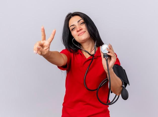 Zadowolona młoda kaukaska chora dziewczyna ubrana w stetoskop patrząc na kamerę mierzącą jej ciśnienie za pomocą ciśnieniomierza robi znak pokoju na białym tle