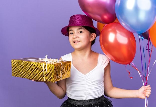 Zadowolona młoda kaukaska dziewczyna w fioletowym kapeluszu imprezowym trzymająca balony z helem i pudełko na prezent na fioletowej ścianie z miejscem na kopię
