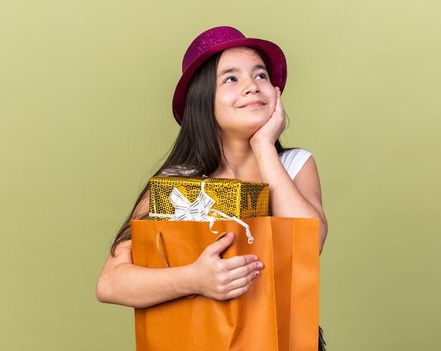 Zadowolona młoda kaukaska dziewczyna w fioletowym kapeluszu imprezowym trzymająca pudełko w torbie na zakupy i kładąca dłoń na twarzy patrząc na bok odizolowana na oliwkowozielonej ścianie z kopią