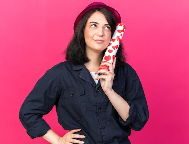 Zadowolona młoda kaukaska dziewczyna w imprezowym kapeluszu, trzymająca armatę konfetti, dotykając twarzą, trzymając rękę na talii, patrząc w górę na różowej ścianie