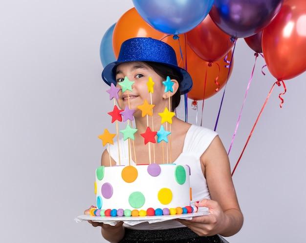 Zadowolona młoda kaukaska dziewczyna w niebieskim kapeluszu imprezowym trzymająca balony z helem i tort urodzinowy na białej ścianie z miejscem na kopię