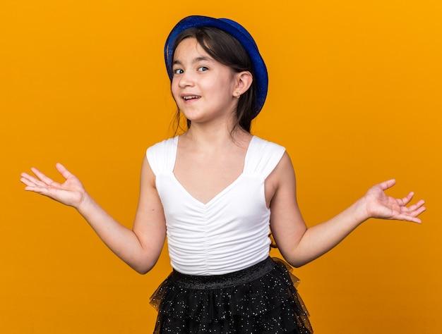 Zadowolona młoda kaukaska dziewczyna w niebieskim kapeluszu imprezowym, trzymająca otwarte ręce, odizolowana na pomarańczowej ścianie z miejscem na kopię