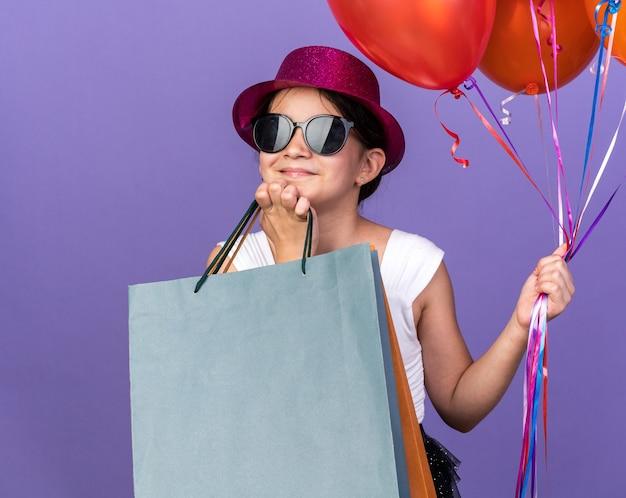 Zadowolona młoda kaukaska dziewczyna w okularach przeciwsłonecznych w fioletowym kapeluszu imprezowym kładąca rękę na brodzie trzymająca balony z helem i torby na zakupy odizolowane na fioletowej ścianie z kopią miejsca