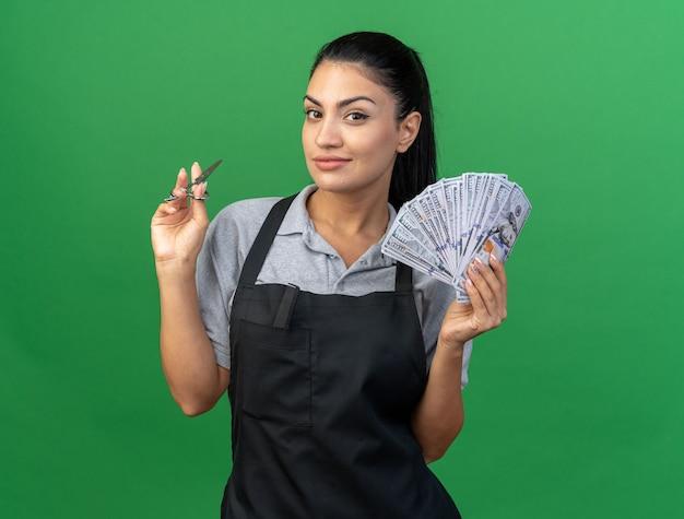 Zadowolona młoda kaukaska fryzjerka w mundurze trzymająca nożyczki i pieniądze patrząca na przód odizolowany na zielonej ścianie