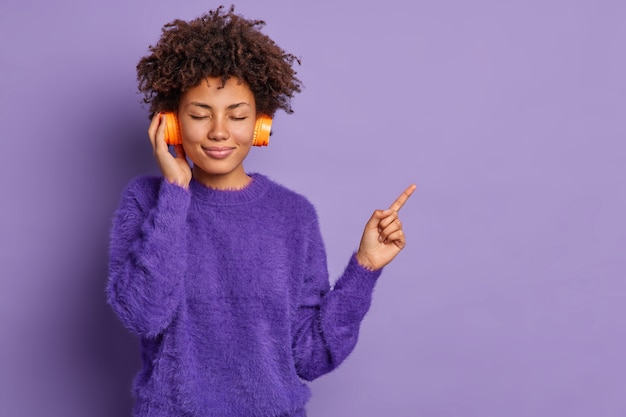 Zadowolona młoda kędzierzawa afroamerykanka ma zamknięte oczy ma kręcone włosy lubi ulubioną melodię ubrana w zwykłe ubrania wskazuje na miejsce kopiowania