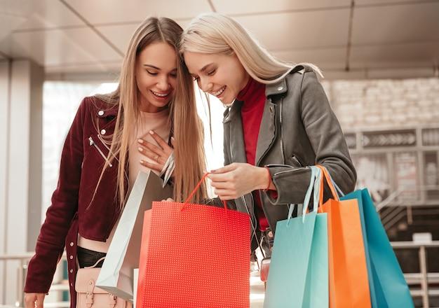 Zadowolona młoda klientka pokazuje dziewczynie zakupy w torbach na zakupy i omawia okazyjną wyprzedaż po zakupach w nowoczesnym centrum handlowym