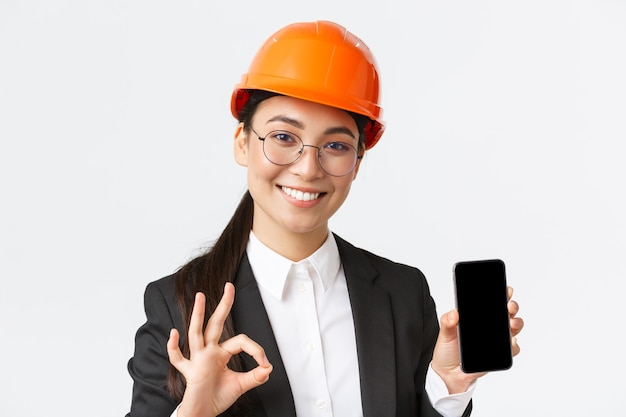 Zadowolona młoda kobieta azjatycka inżynier, architekt w garniturze i kasku pokazująca ekran telefonu komórkowego i wykonująca dobry gest, zatwierdzająca, polecająca aplikację, białe tło