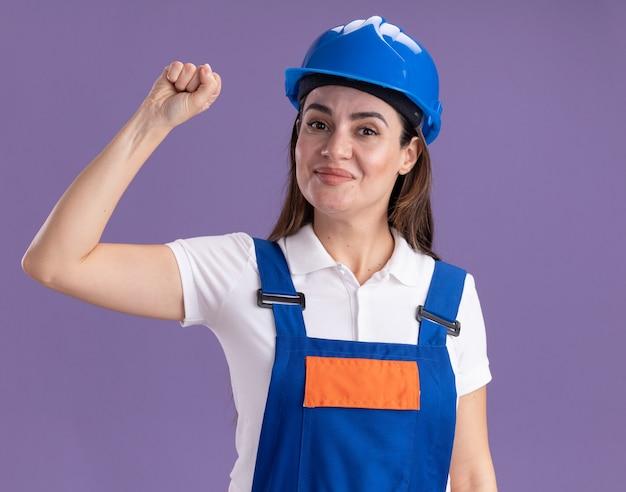 Zadowolona młoda kobieta budowniczy w mundurze pokazując gest tak na białym tle na fioletowej ścianie