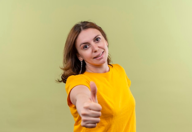 Zadowolona młoda kobieta dorywczo pokazująca kciuk do góry na odosobnionej zielonej przestrzeni z miejscem na kopię