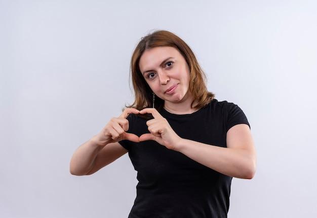 Zadowolona młoda kobieta dorywczo robi znak serca na odosobnionej białej przestrzeni