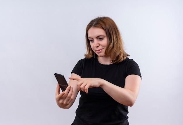Zadowolona młoda kobieta dorywczo trzymając telefon komórkowy i wskazując na niego na odosobnionej białej przestrzeni z kopią miejsca