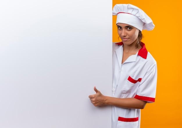 Zadowolona młoda kobieta kucharz ubrana w mundur szefa kuchni trzymając białą ścianę jej kciuk z miejsca na kopię