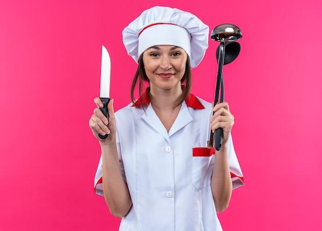 Zadowolona młoda kobieta kucharz w mundurze szefa kuchni trzymająca nóż z kadzią na białym tle na różowym tle