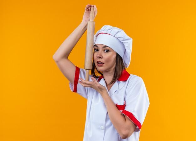 Zadowolona młoda kobieta kucharz w mundurze szefa kuchni trzymająca wałek do ciasta na pomarańczowej ścianie