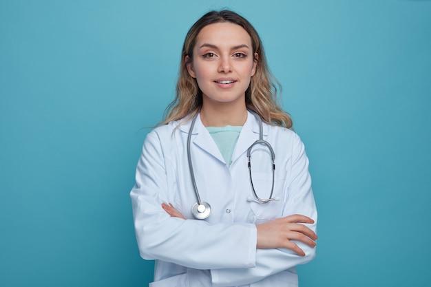 Zadowolona młoda kobieta lekarz ubrana w szlafrok medyczny i stetoskop wokół szyi, stojąca z zamkniętą posturą