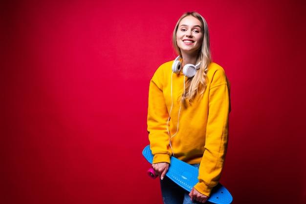 Zadowolona młoda kobieta niosąca deskorolkę na ramieniu i uśmiechnięta przed czerwoną ścianą