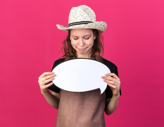 Zadowolona młoda kobieta ogrodniczka w kapeluszu ogrodniczym, trzymająca i patrząca na dymek