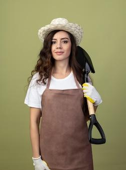 Zadowolona młoda kobieta ogrodniczka w mundurze na sobie kapelusz ogrodniczy i rękawiczki trzyma łopatę na białym tle na oliwkowej ścianie