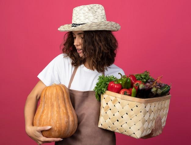 Zadowolona młoda kobieta ogrodniczka w mundurze na sobie kapelusz ogrodniczy, trzymając kosz warzyw i patrząc na dynię w dłoni na różowym tle