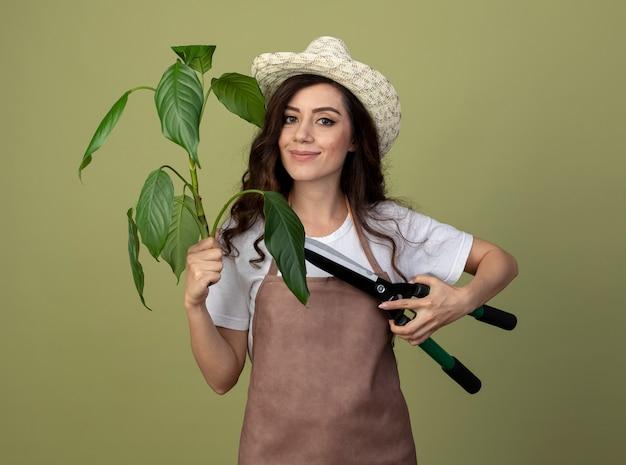 Zadowolona młoda kobieta ogrodniczka w mundurze w kapeluszu ogrodniczym trzyma maszynki do strzyżenia roślin i ogrodu na białym tle na oliwkowej ścianie