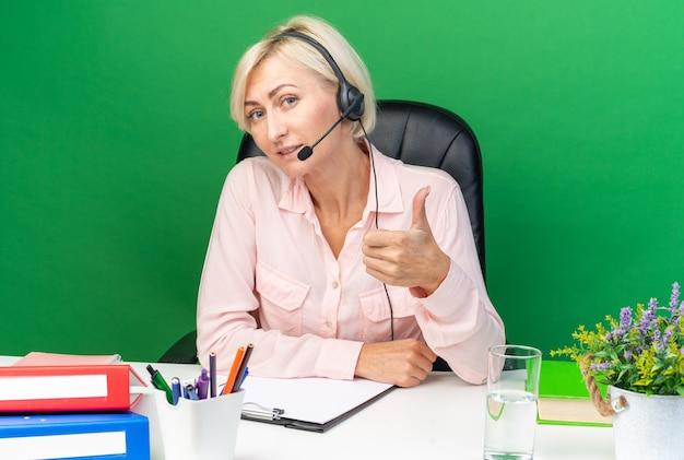 Zadowolona młoda kobieta operatora call center nosząca zestaw słuchawkowy siedzący przy stole z narzędziami biurowymi pokazującymi kciuk w górę