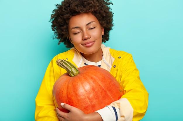 Zadowolona młoda kobieta rasy mieszanej trzyma zebraną na pomarańczowo dynię, nosi swobodny żółty płaszcz przeciwdeszczowy, ma zamknięte oczy, pozuje na niebieskim tle.