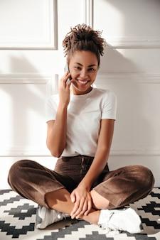 Zadowolona młoda kobieta rozmawia na smartfonie