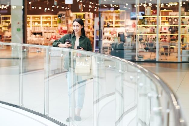 Zadowolona młoda kobieta stojąca przy poręczy i przy użyciu smartfona, czekając na przyjaciela w centrum handlowym